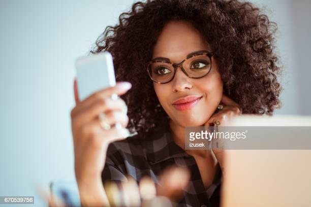 happy young woman with glasses using smart phone