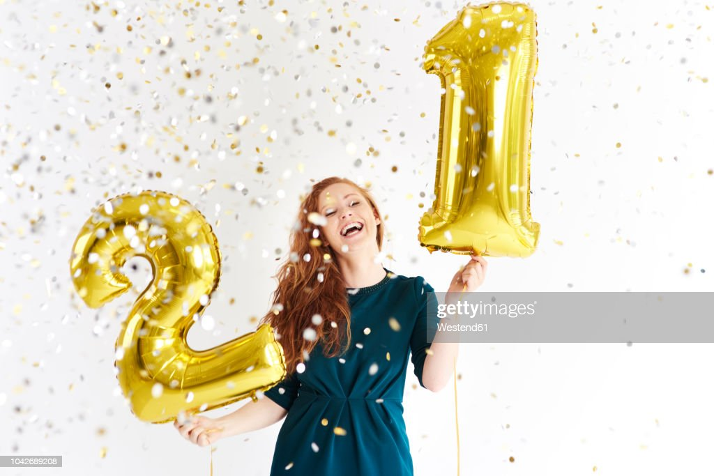 Happy young woman with golden balloons celebrating her birthday : Foto de stock