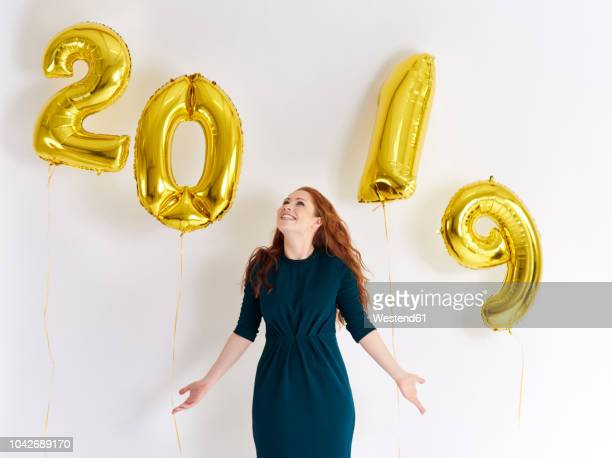 happy young woman with golden balloons forming the date '2019' - 2019 stock-fotos und bilder