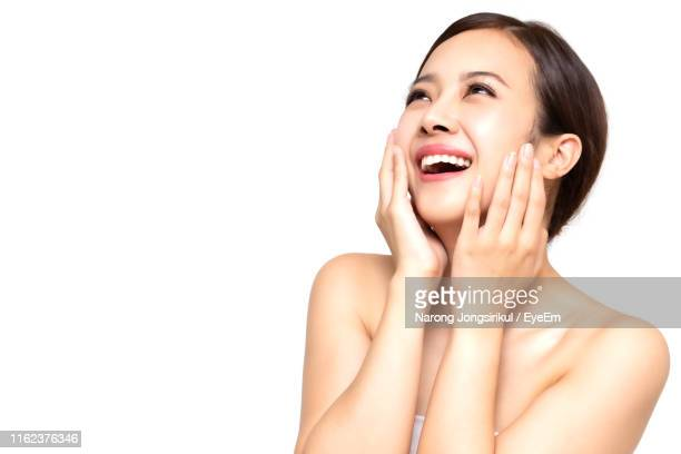 happy young woman with hands on cheeks standing against white background - 人体部位 ストックフォトと画像