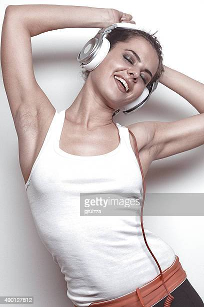 Happy young woman with headphones, listening to music and dancin