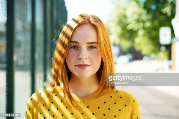 happy young woman with headphones, next to fence. - 20 29 years stock pictures, royalty-free photos & images