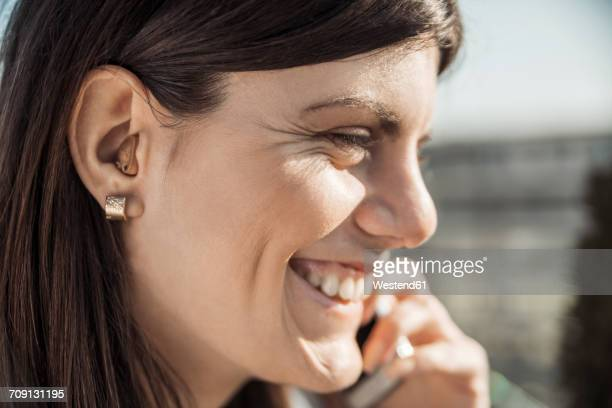 Happy young woman with hearing aid on the phone