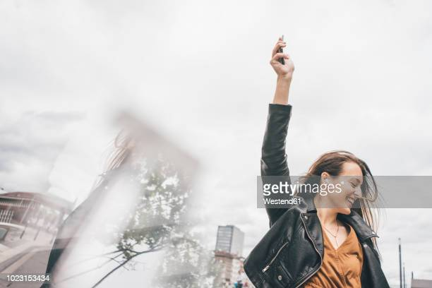happy young woman with in-ear phones and cell phone - freiheit stock-fotos und bilder