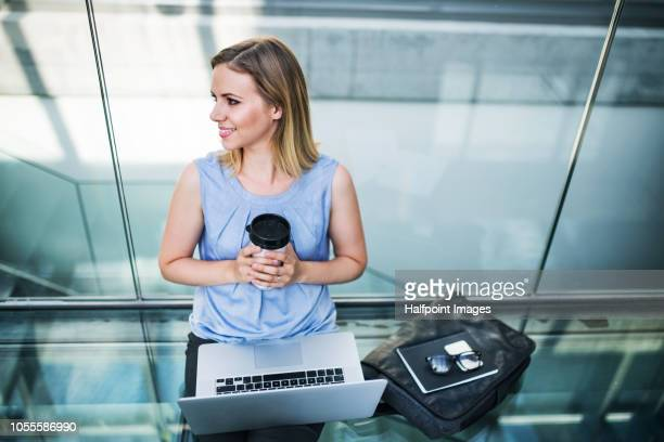 Happy young woman with laptop sitting on the floor in the modern building, holding coffee in travel mug.