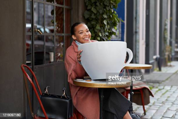 happy young woman with large coffee cup at sidewalk cafe - large stock pictures, royalty-free photos & images