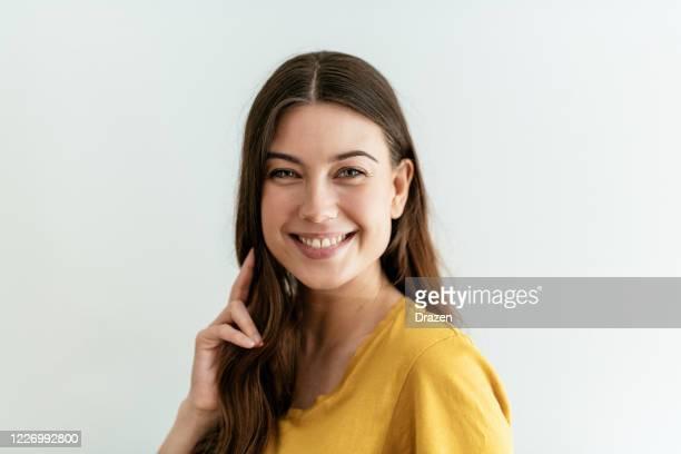 黄色のtシャツで長い髪を持つ幸せな若い女性 - 素顔 ストックフォトと画像