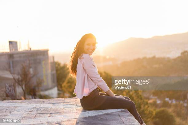 Happy young woman with long hair sitting on a wall at sunset