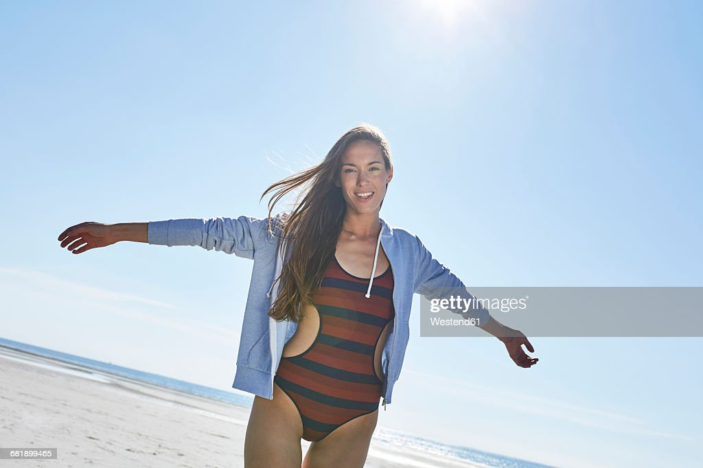 Happy young woman with outstretched arms on the beach : Stock Photo