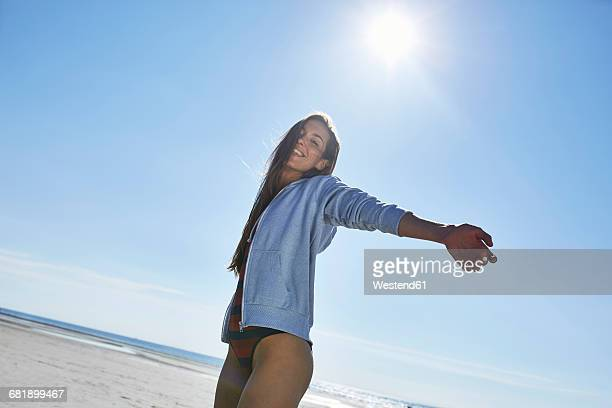 Happy young woman with outstretched arms on the beach
