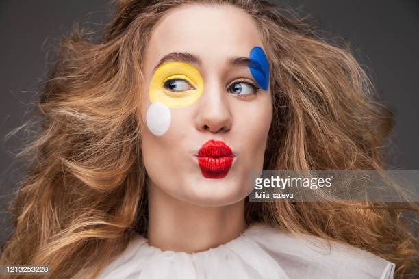 happy young woman with painted face in clown costume sending air kiss - clown stock-fotos und bilder