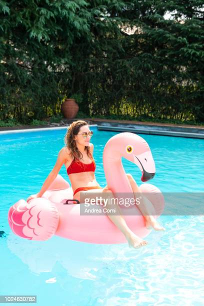 happy young woman with pink flamingo float in swimming pool - standing water stock pictures, royalty-free photos & images