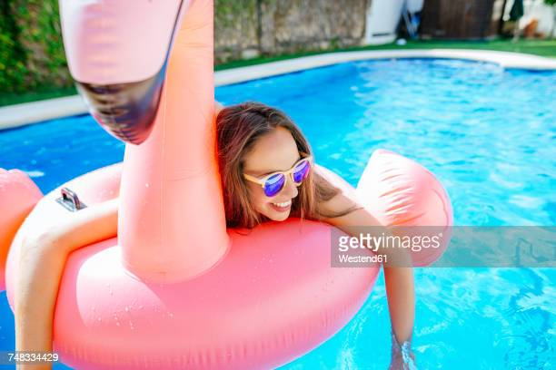 Happy young woman with pink flamingo float in swimming pool
