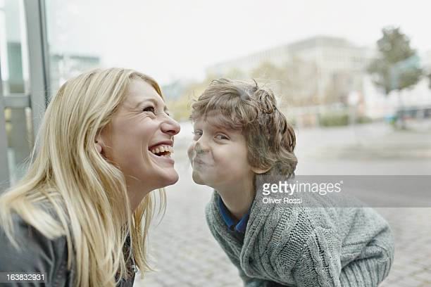 Happy young woman with son behind windowpane