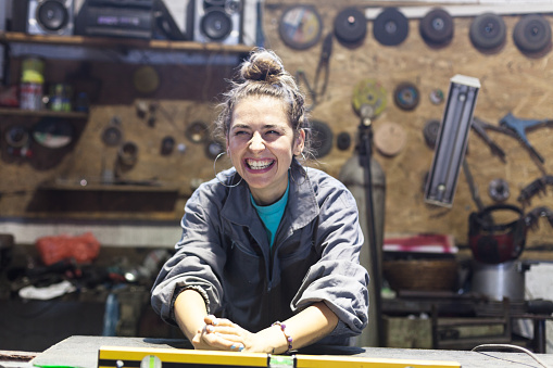 happy young woman working in a workshop 1051469440