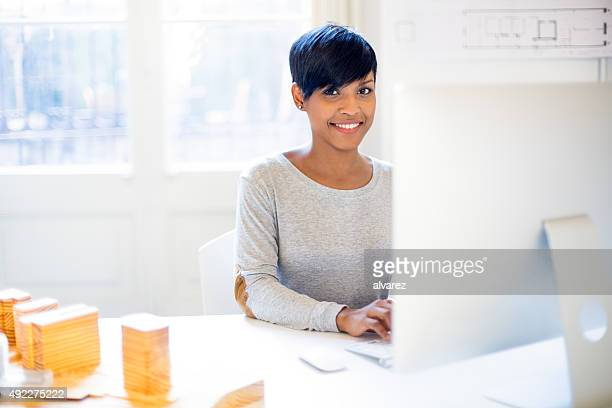Happy young woman working on computer