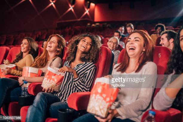 happy young women at cinema - comedy film stock photos and pictures