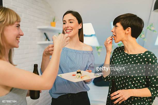 Happy Young Women At The Party Eating Sushi.