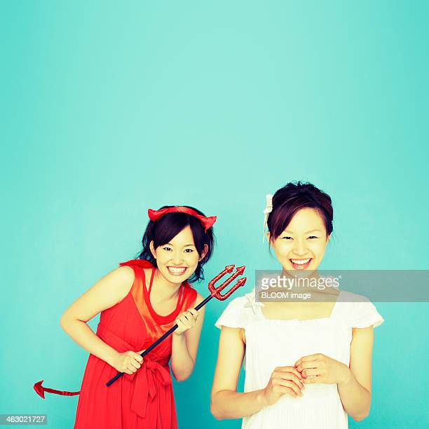 happy young women dressed as devil and angel - devil costume stockfoto's en -beelden