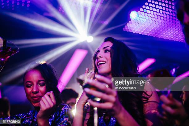 Happy young women drinking cocktail in night club party