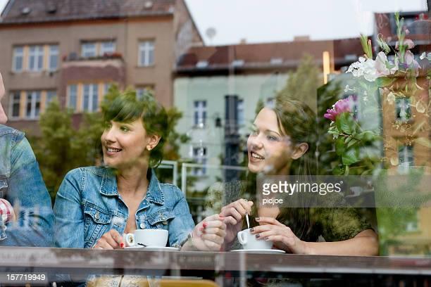 Glückliche junge Frauen trinken Kaffee im Café
