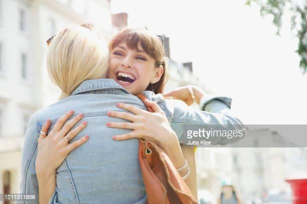 happy young women friends hugging on sunny urban sidewalk - 和解 ストックフォトと画像