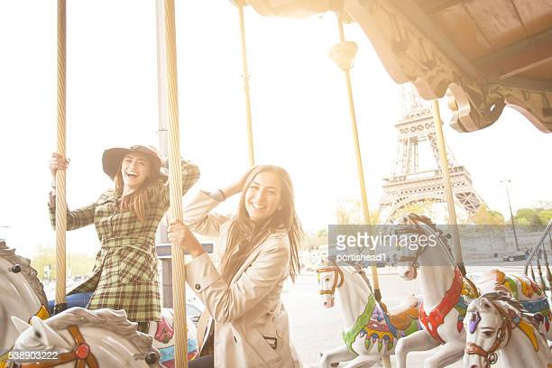 Happy young women having fun on carousel at Eiffel tower