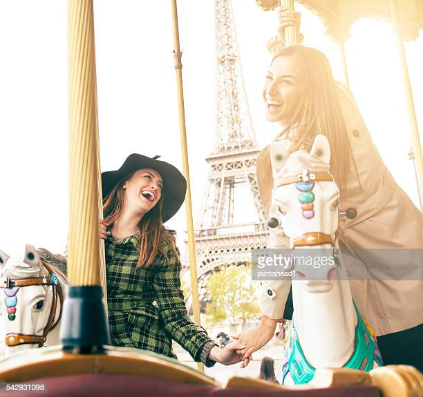 Happy young women having fun on marry-go-round at Eiffel Tower