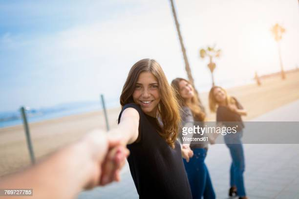 Happy young women holding hands outdoors