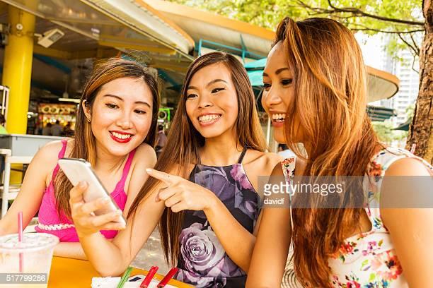 Heureux jeunes femmes à Singapour avec un téléphone portable