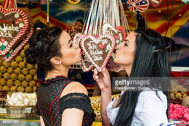 Happy Young Women Kissing Candy Heart In Market Stall At Oktoberfest
