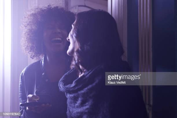 happy young women looking at smartphone at party - accessibility stock pictures, royalty-free photos & images