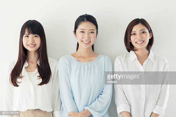 happy young women standing by wall - three people ストックフォトと画像