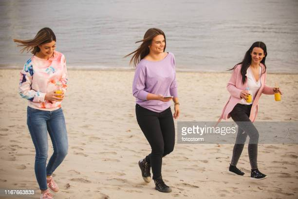 Happy young women taking a walk on the beach together