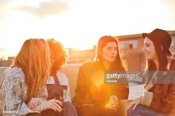 glückliche junge frauen sprechen auf dem dach - sonnig stock-fotos und bilder