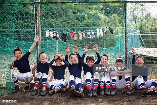 happy youth baseball players sitting together