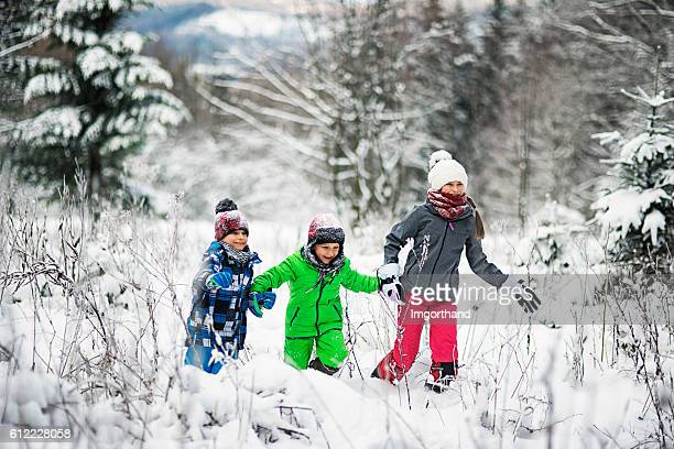 Happyt children running in winter forest
