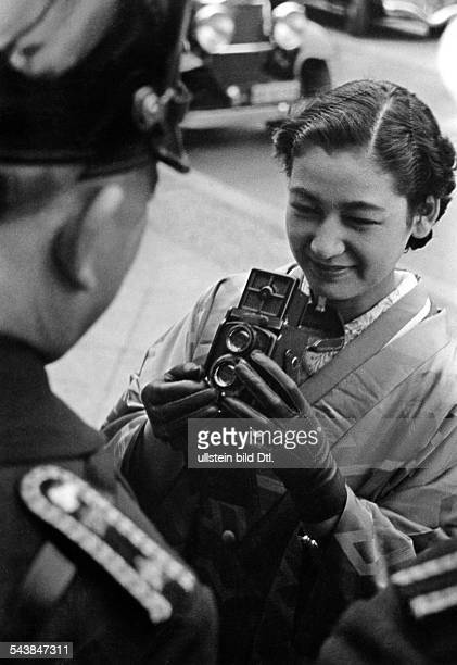 Hara Setsuko Actress Japan*nee Masae Aida is photographing a policeman with her Rolleiflex camera during her visit to Berlin Photographer Werner...