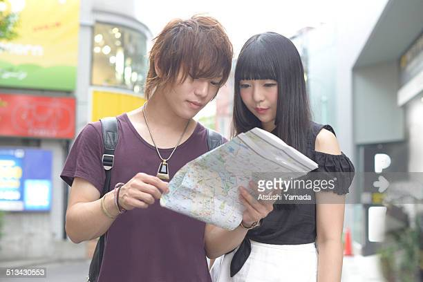 Harajuku couple looking at map on street