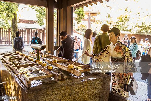 Harajuku, Meiji-jingu (Meiji Shrine), woman with typical kimono dress near the water font (Temizuya)