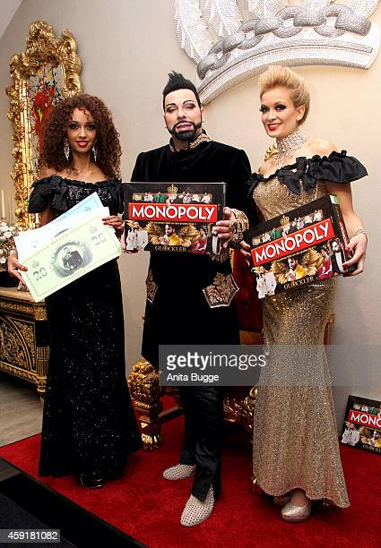 Harald Gloeoeckler poses with models as he presents the Gloeoeckler Monopoly game at the Gloeoeckler store on November 18 2014 in Berlin Germany