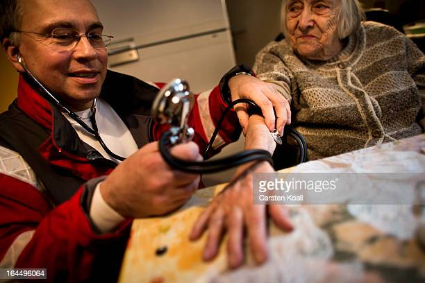 Harald Gross who works for the German Red Cross takes the blood pressure of 100yearold senior citizen Frida Fiedler in order to illustrate the...