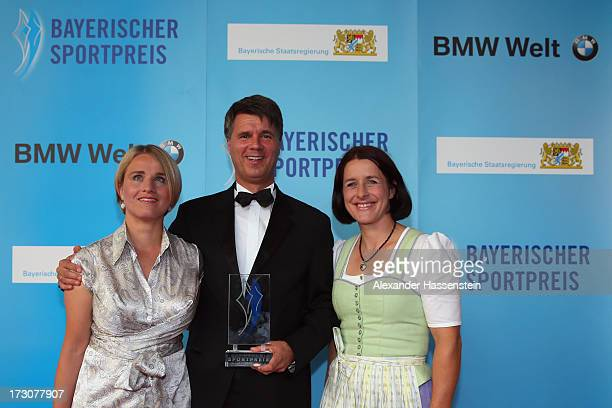 Harald Krueger Board of Management member for Production of BMW AG poses with the Bavarian Sportaward 2013 beside Verena Bentele and Uschi Disl after...