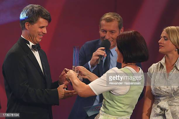 Harald Krueger Board of Management member for Production of BMW AG receives the Bavarian Sportaward 2013 from Uschi Disl beside presenter Markus...