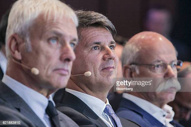 Harald Krueger chief executive officer of Bayerische Motoren Werke AG center looks on as he sits flanked by Matthias Mueller chief executive officer...