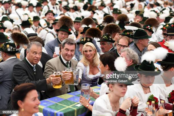 Harald Kuehn member of the Bavarian parliament Markus Soeder Prime Minister of Bavaria and his wife Karin sit in a beer tent during the 125th...