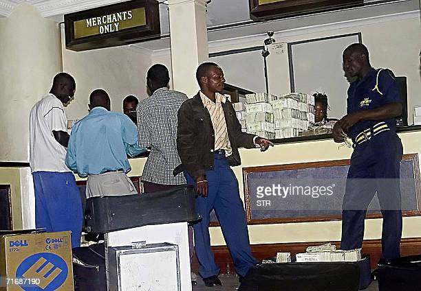 Depositors take turns to hand in boxfuls of the old bearer cheques at a bank in central Harare 21 August 2006 as Zimbabwe's central bank phased out...