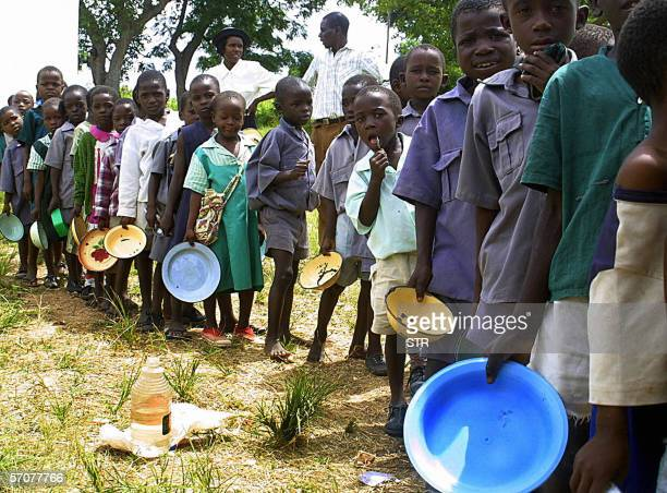 Schoolchildren wait in a queue for porridge provided by the Irish aid agency GOAL through the World Food Programme to supplement the food they eat at...