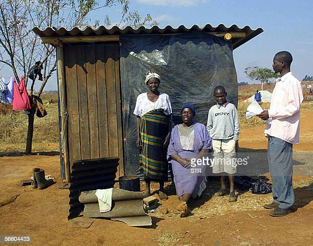 This picture taken 08 August 2005 on the outskirts of the Zimbabwean capital Harare shows residents of a shantytown posing in front of their...