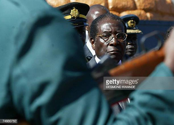 Zimbabwean President Robert Mugabe looks on as the army parade at the burial of national hero Paul Gunda in Harare 27 June 2007 where he warned that...